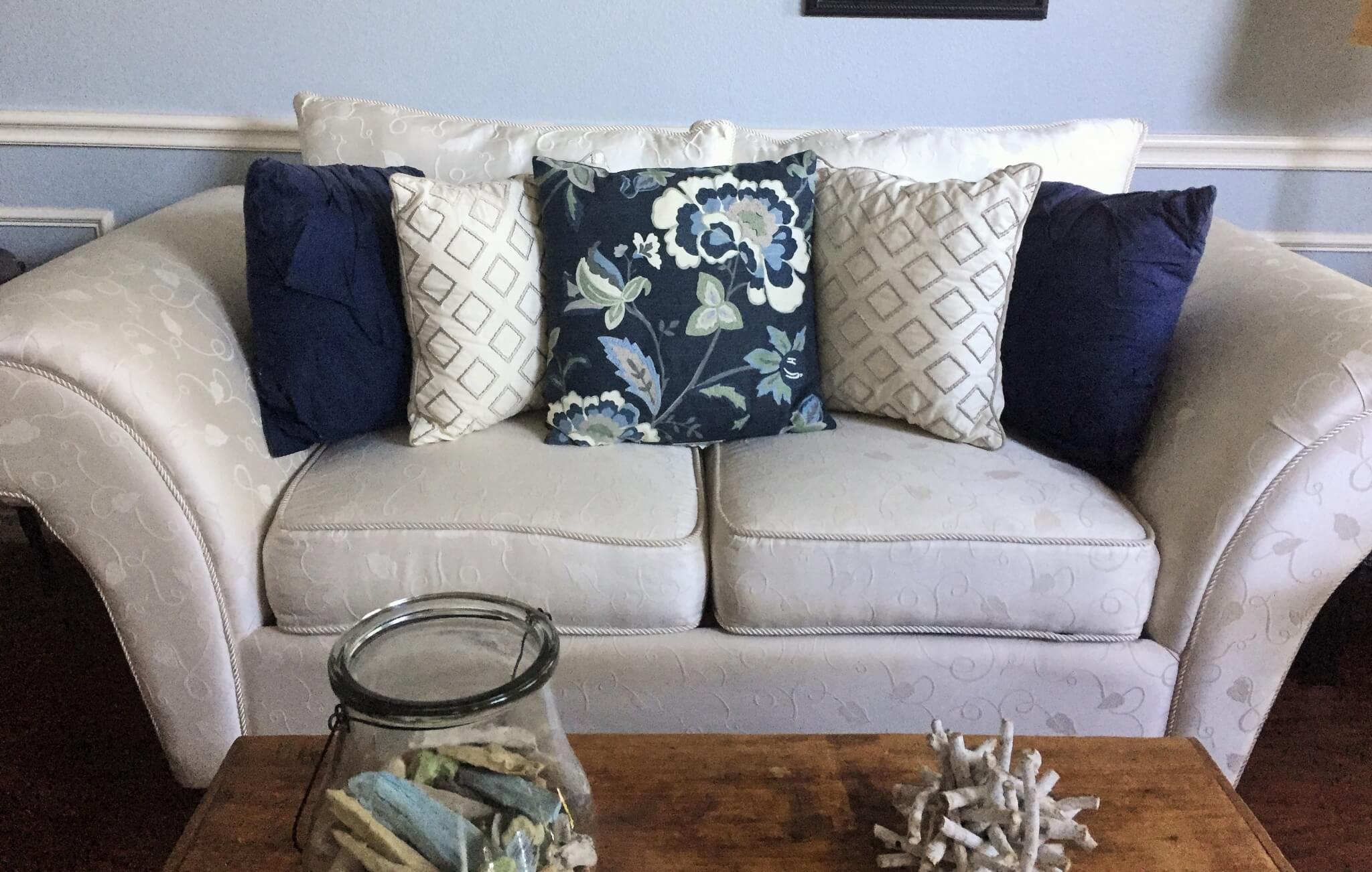 Couch with large print, small print, and solid throw pillows.