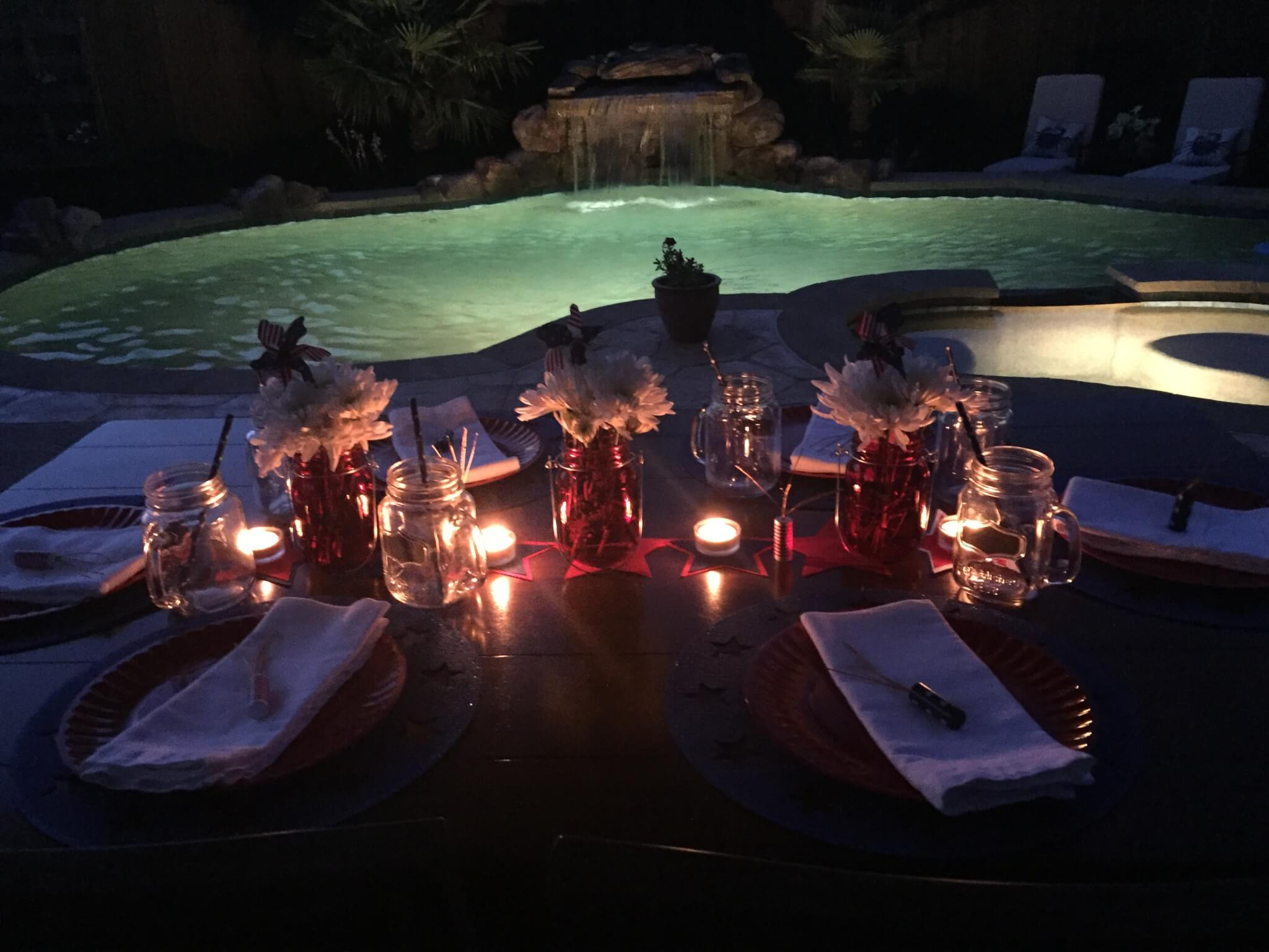 Evening view of patriotic tablescape on patio in front of lit up pool.