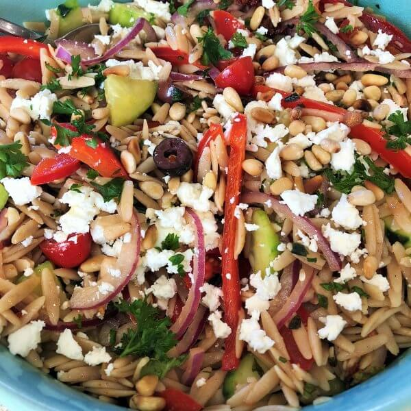 Mediterranean orzo salad with sun-dried tomatoes, pine nuts, and feta is made with plenty of fresh vegetables and herbs. It's tossed with a light lemony dressing.