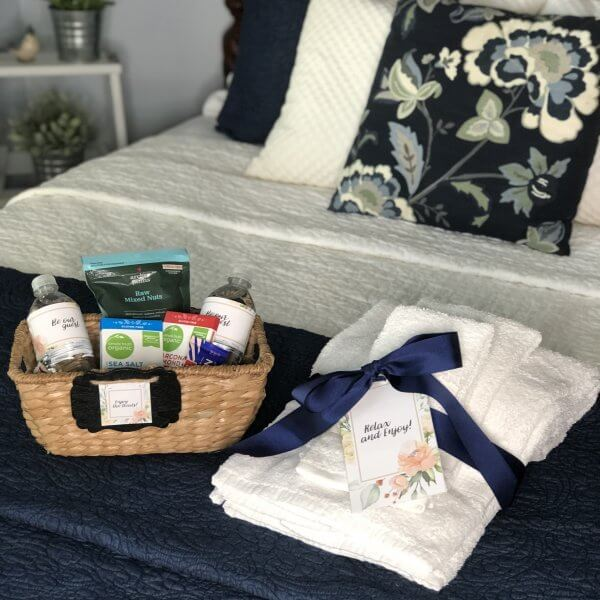 Guest room bed with snack basket and guest towels