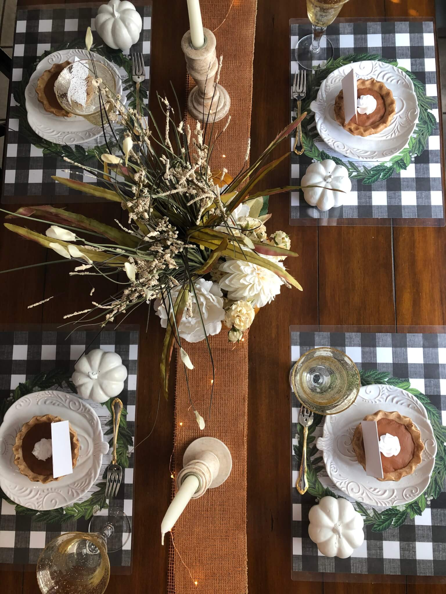 overhead of pumpkin and buffalo check fall tablescape