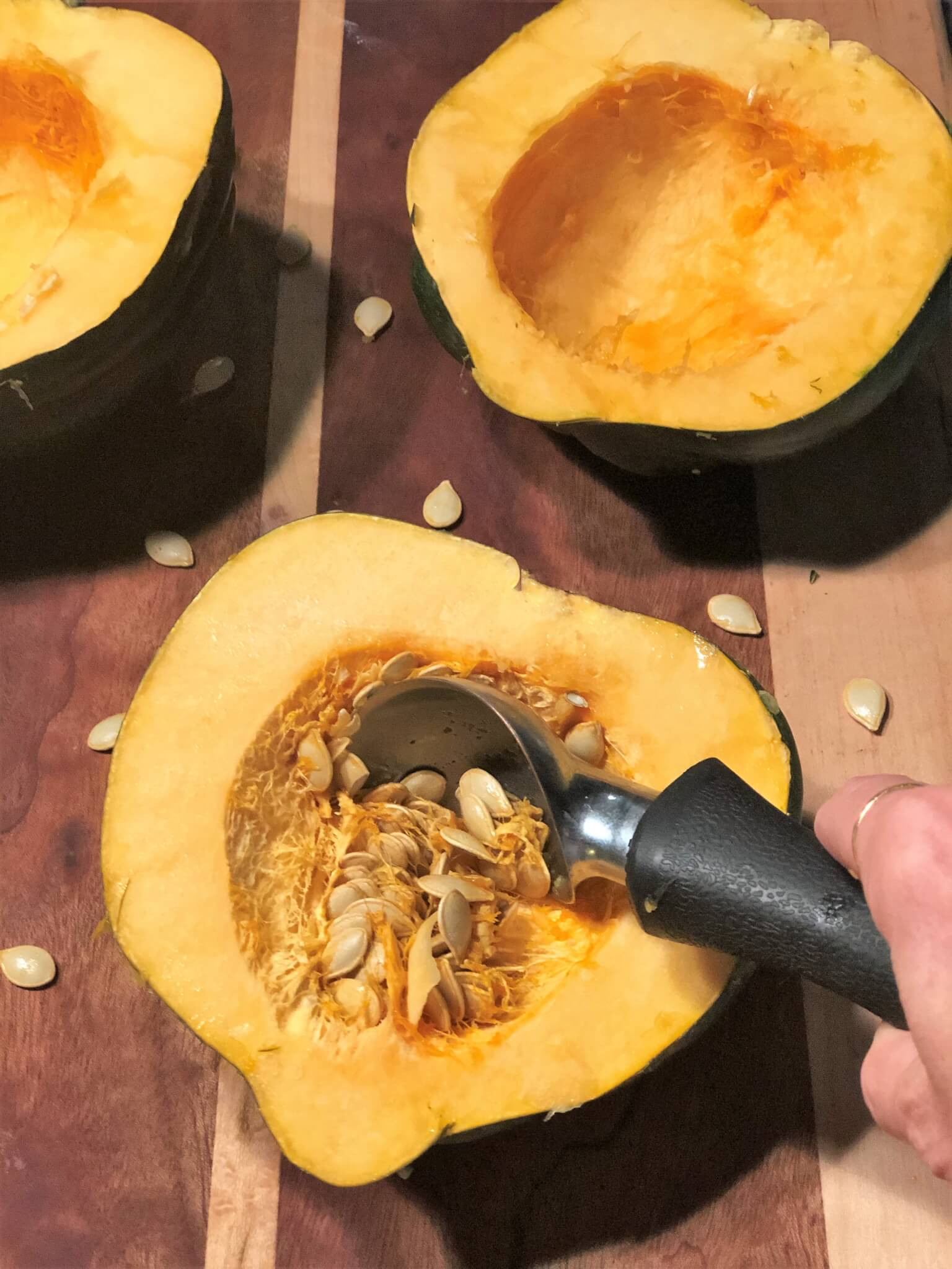 Scooping seeds from acorn squash to make stuffed acorn squash